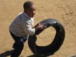Pheto playing with his tire; little kids roll tires around for fun